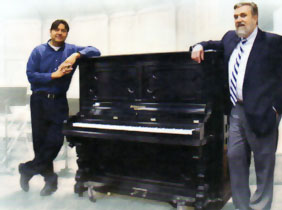 Clint Hughes and Douglas Wilson standing next to restored upright piano